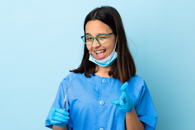 Młoda brunetka kobieta dentysta rasy mieszanej gospodarstwa narzędzia