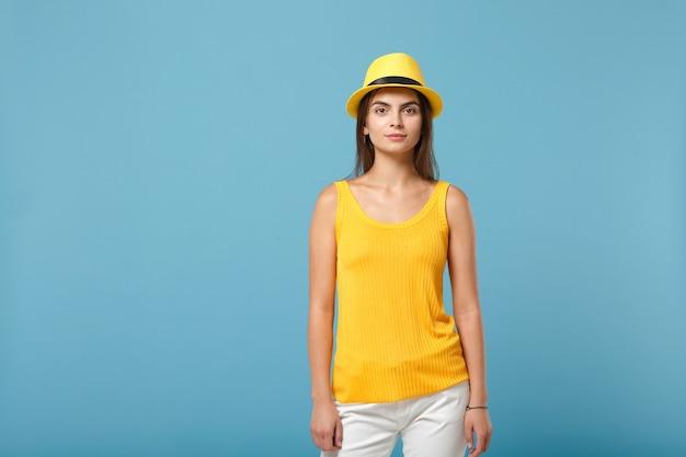 Młoda brunetka kobieta dziewczyna w letnim kapeluszu dorywczo żółte ubrania pozowanie na białym tle na niebieski portret ściany. koncepcja życia szczere emocje ludzi.