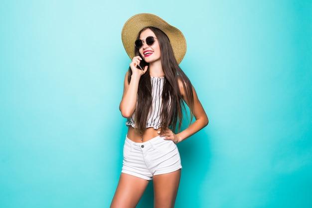 Młoda brunetka kobieta dziewczyna w ubranie pozowanie rozmawia przez telefon komórkowy na białym tle na turkusowym tle portret studio. ludzie koncepcja stylu życia szczere emocje.