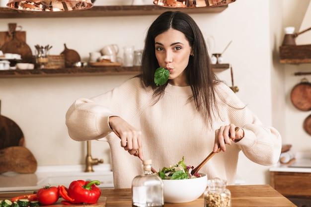Młoda brunetka kobieta gotowanie i jedzenie zdrowej zielonej sałatki z warzywami w domu