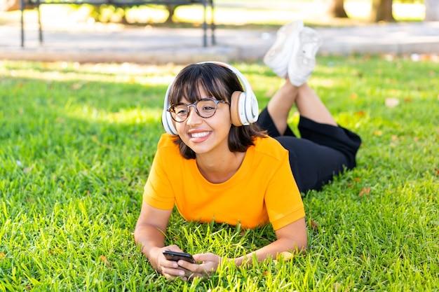 Młoda brunetka kobieta na zewnątrz słucha muzyki za pomocą telefonu komórkowego i szczęśliwa