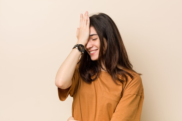 Młoda brunetka kobieta o beżowej ścianie, zapominając o czymś, uderzając dłonią w czoło i zamykając oczy.