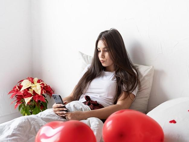 Młoda brunetka kobieta obudzona w łóżku z czerwonymi balonami w kształcie serca i tekstami dekoracji