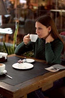 Młoda brunetka kobieta picia kawy w kawiarni i jedzenie deseru