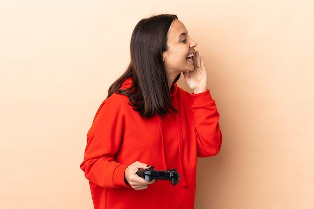 Młoda brunetka kobieta rasy mieszanej bawi się kontrolerem gier wideo na odizolowanej ścianie krzycząc z szeroko otwartymi ustami