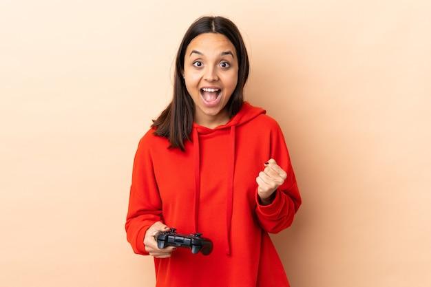 Młoda brunetka kobieta rasy mieszanej bawi się kontrolerem gier wideo na odizolowanej ścianie świętuje zwycięstwo