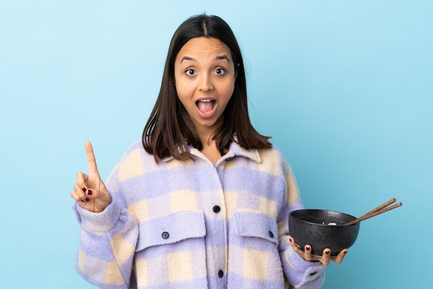 Młoda brunetka kobieta rasy mieszanej na odosobnionej niebieskiej ścianie wskazując na świetny pomysł, trzymając miskę makaronu pałeczkami.