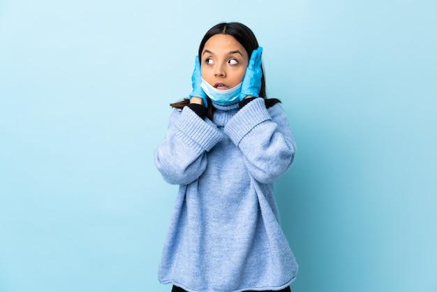 Młoda brunetka kobieta rasy mieszanej ochrony przed koronawirusem z maską i rękawiczkami na pojedyncze niebieskie ściany sfrustrowane i obejmujące uszy