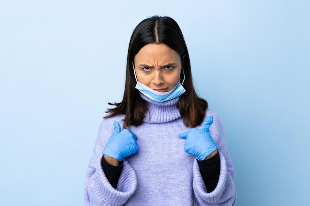 Młoda brunetka kobieta rasy mieszanej ochrony przed koronawirusem z maską i rękawiczkami na pojedyncze niebieskie ściany, wskazując na siebie