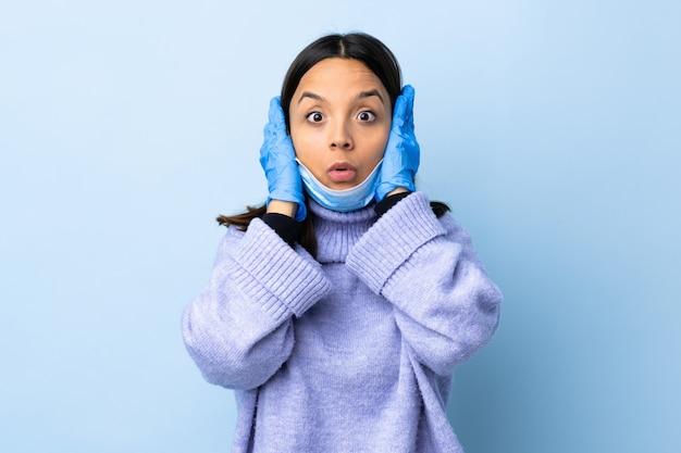 Młoda brunetka kobieta rasy mieszanej ochrony z maską i rękawice na niebieską ścianą sfrustrowani i obejmujące uszy