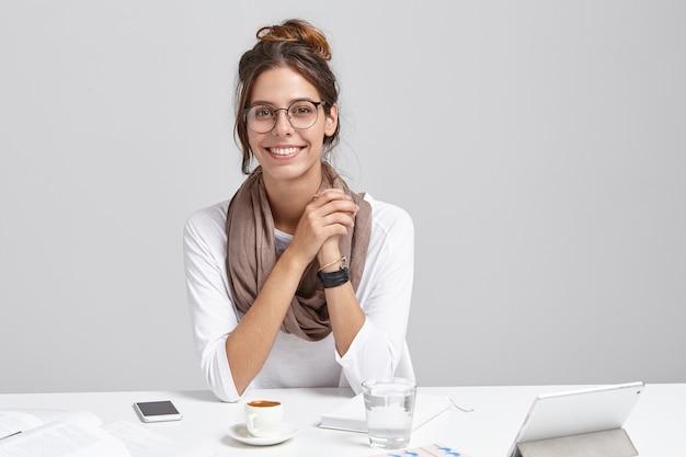 Młoda brunetka kobieta siedzi przy biurku