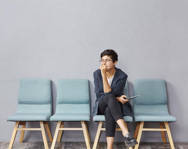 Młoda brunetka kobieta siedzi w poczekalni
