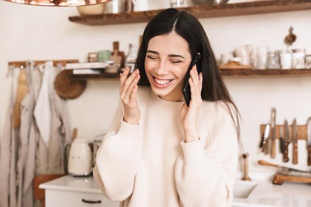 Młoda brunetka kobieta śmiejąc się, trzymając i rozmawiając na smartfonie w stylowej kuchni w domu