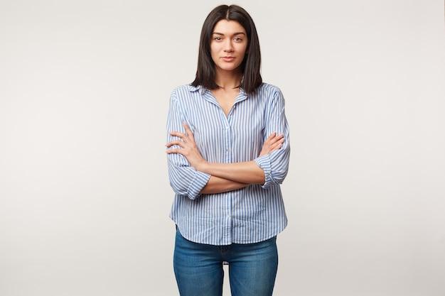 Młoda brunetka kobieta, spokojna, uważna, słucha z szacunkiem, zwraca uwagę, stoi z rękami skrzyżowanymi, ubrana w niebieskie dżinsy i koszulę w paski na białym tle