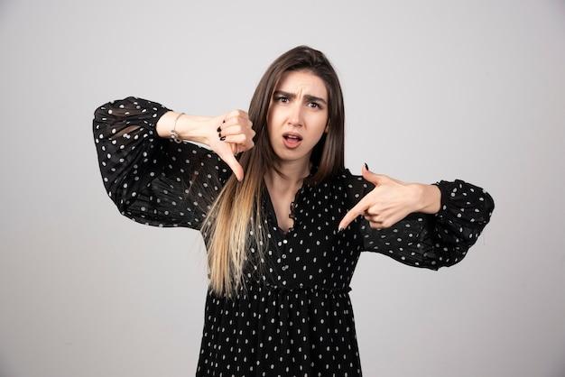 Młoda brunetka kobieta stoi i pokazuje odrzucenie i negatyw z kciukiem w dół gestem.