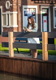 Młoda brunetka kobieta stojąca na drewnianym moście z tabletem