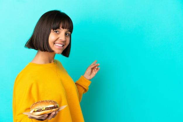 Młoda brunetka kobieta trzyma burgera na białym tle, wskazując do tyłu