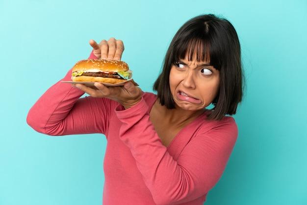 Młoda brunetka kobieta trzyma burgera na białym tle