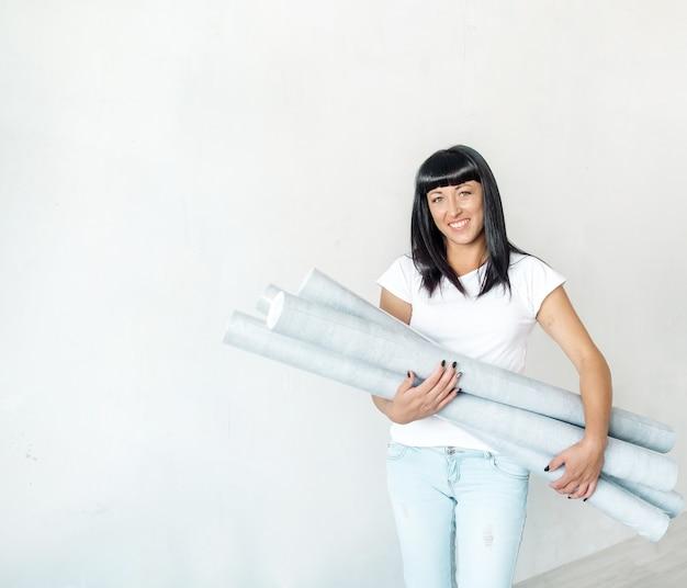 Młoda brunetka kobieta trzyma rolki tapety w dłoniach na tle białej ściany