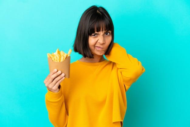 Młoda brunetka kobieta trzyma smażone frytki na odosobnionym niebieskim tle, mając wątpliwości