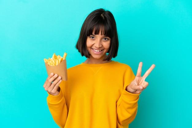 Młoda brunetka kobieta trzyma smażone frytki na odosobnionym niebieskim tle, uśmiechając się i pokazując znak zwycięstwa