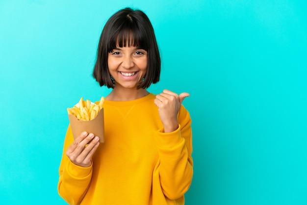 Młoda brunetka kobieta trzyma smażone frytki na odosobnionym niebieskim tle, wskazując na bok, aby zaprezentować produkt