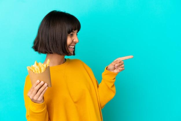 Młoda brunetka kobieta trzyma smażone frytki na odosobnionym niebieskim tle, wskazując palcem na bok i prezentując produkt