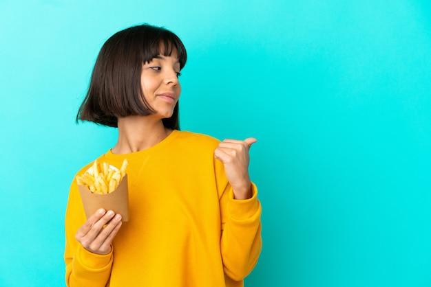 Młoda brunetka kobieta trzyma smażone frytki nad odosobnioną niebieską ścianą skierowaną w bok, aby zaprezentować produkt