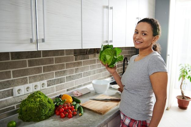 Młoda brunetka kobieta trzyma świeżą kapustę i uśmiecha się do kamery, stojąc przed domową kuchnią