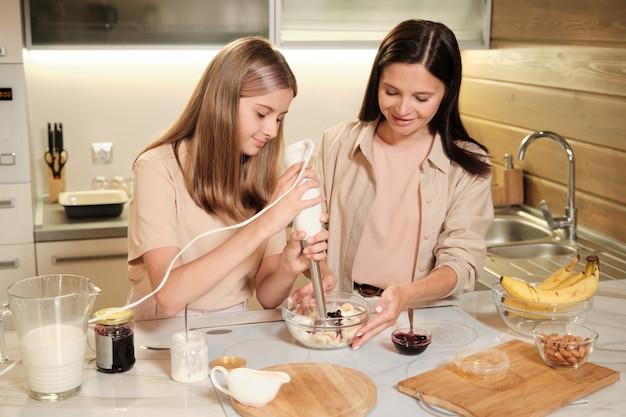 Młoda brunetka kobieta trzyma szklaną miskę, podczas gdy jej nastoletnia córka z elektrycznym mikserem mieszania składników domowych lodów