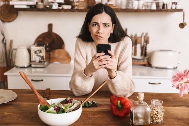 Młoda brunetka kobieta trzymając smartfon podczas gotowania zdrowej zielonej sałatki z warzywami w stylowej kuchni w domu