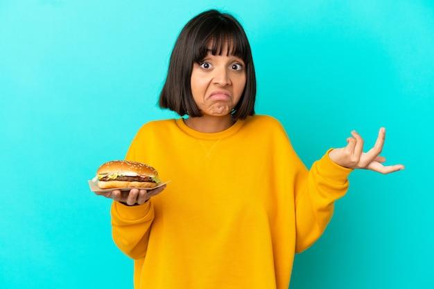 Młoda brunetka kobieta trzymająca burgera na białym tle, mająca wątpliwości podczas podnoszenia rąk