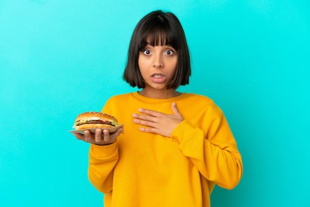 Młoda brunetka kobieta trzymająca burgera na białym tle zaskoczona i zszokowana, patrząc w prawo