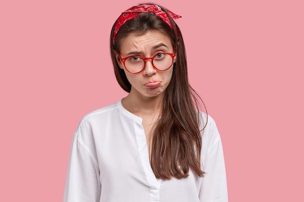 Młoda brunetka kobieta ubrana w czerwoną chustkę i okulary