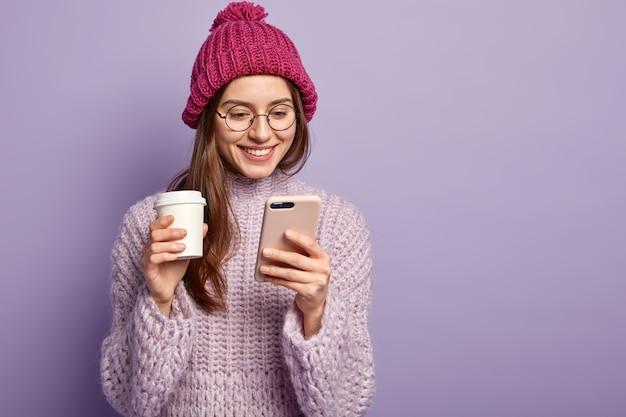 Młoda brunetka kobieta ubrana w fioletowy sweter i trzymając filiżankę kawy