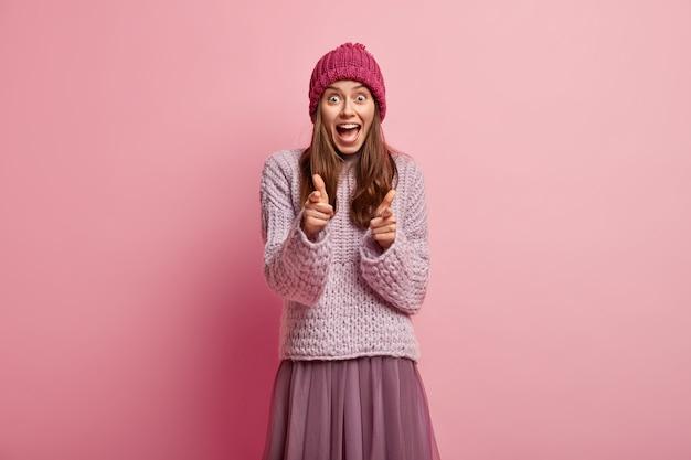 Młoda brunetka kobieta ubrana w kolorowe zimowe ubrania