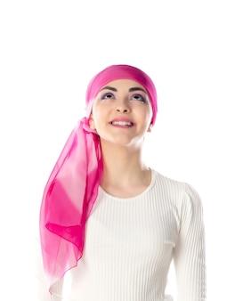 Młoda brunetka kobieta ubrana w różowy szalik na głowie na białym tle
