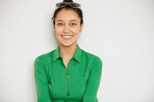 Młoda brunetka kobieta ubrana w zieloną koszulę