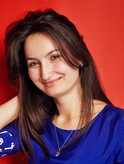 Młoda brunetka kobieta uśmiecha się do kamery na czerwono
