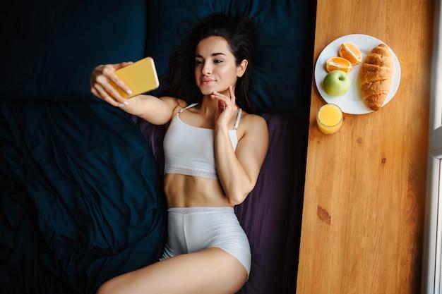 Młoda brunetka kobieta w białej bieliźnie ma śniadanie na drewnianym parapecie