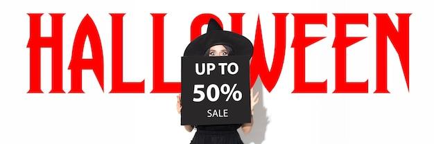 Młoda brunetka kobieta w czarnym kapeluszu. atrakcyjna modelka na białym tle wzywająca do sprzedaży. czarny piątek, cyber poniedziałek, sprzedaż, koncepcja jesień. ulotka do reklamy. do 50 procent.