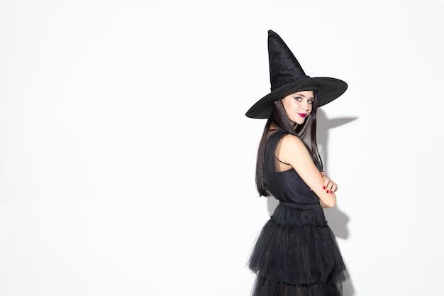 Młoda brunetka kobieta w czarnym kapeluszu i kostiumie na białym tle