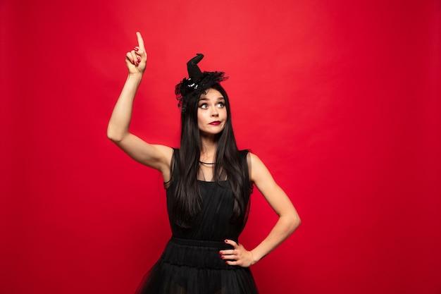 Młoda brunetka kobieta w czarnym kapeluszu i kostiumu na czerwonym tle. atrakcyjna kaukaska modelka. halloween, czarny piątek, cyber poniedziałek, sprzedaż, koncepcja jesień. miejsce. wskazując w górę.