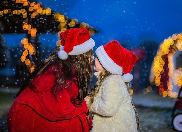 Młoda brunetka kobieta w czerwonym płaszczu i czapce świętego mikołaja całuje młodą córkę w beżowym płaszczu i czapce świętego mikołaja. śnieg w tle.
