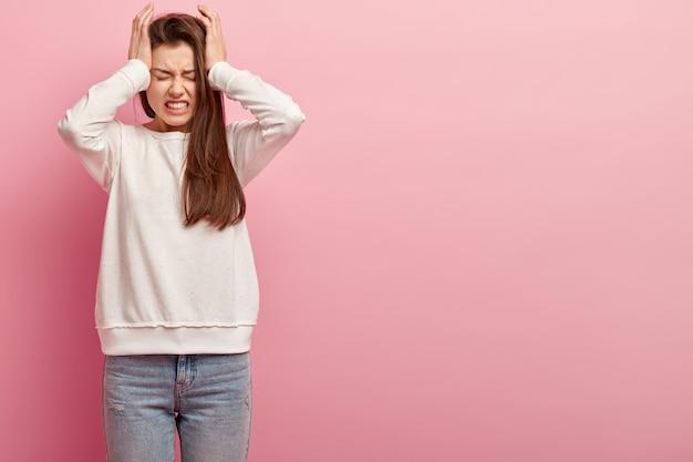 Młoda brunetka kobieta w dżinsach i swetrze