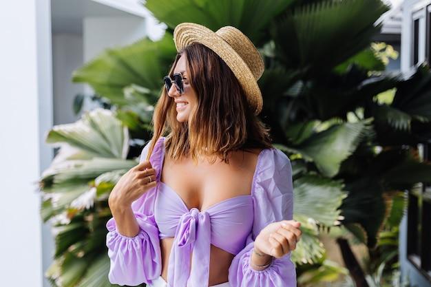 Młoda brunetka kobieta w fioletowych białych spodenkach crop top z długim rękawem