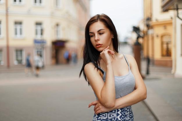 Młoda brunetka kobieta w letnie ubrania na zewnątrz w mieście