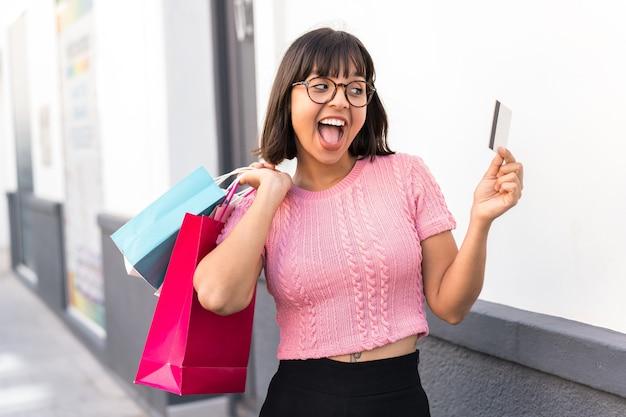 Młoda brunetka kobieta w mieście trzyma torby na zakupy i kartę kredytową
