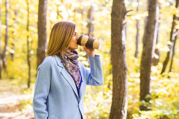 Młoda brunetka kobieta w niebieskim płaszczu stojąc w parku przy filiżance kawy