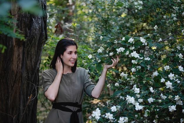 Młoda brunetka kobieta w zielonej sukience przy krzaku jaśminu z białymi pachnącymi kwiatami w parku